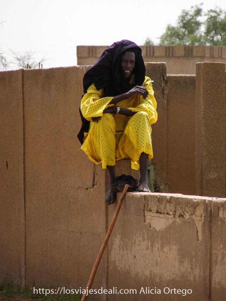 hombre muy delgado con traje amarillo chillón y turbante morado en la cabeza sentado en un muro de adobe en el mercado africano de gorom gorom