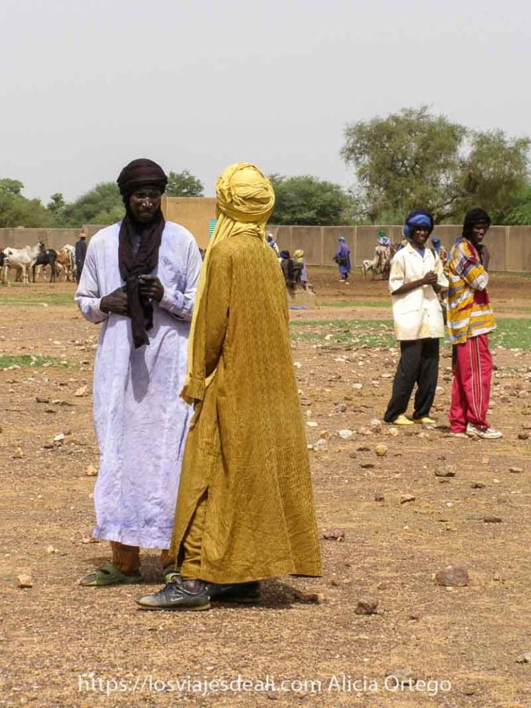 dos tuareg vestidos de color amarillo y morado hablando en el mercado africano de gorom gorom