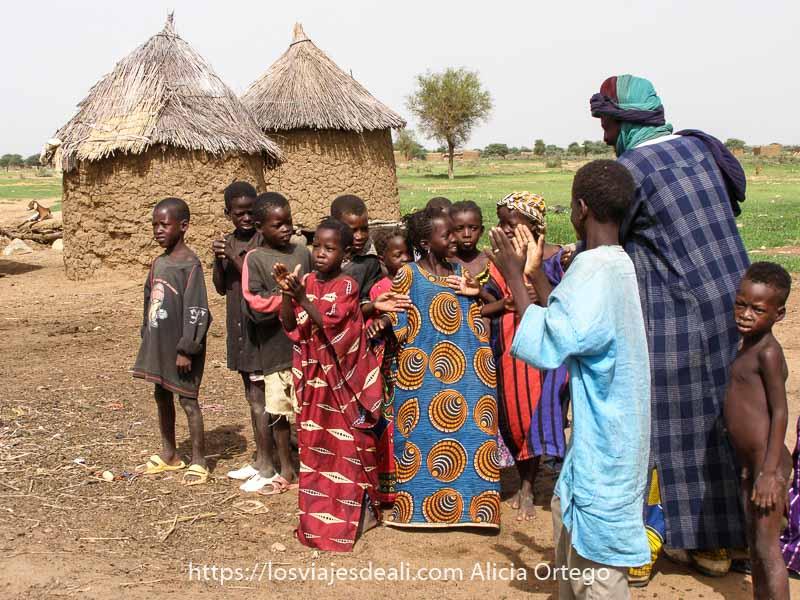 hombre colocando a un grupo de niños de unos 6 o 7 años para que canten una canción