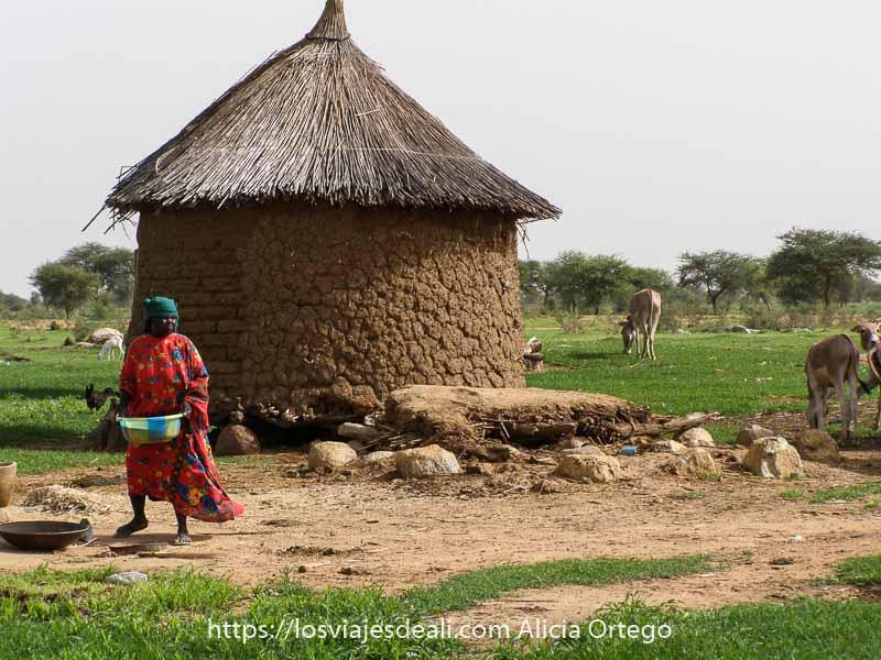 mujer con vestido rojo estampado llevando un barreño junto a una casita circular de adobe y techo de paja terminado en punta