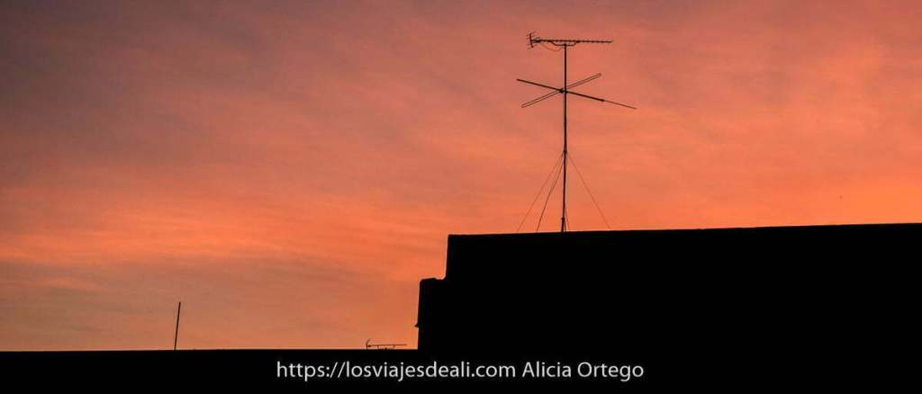 antena de televisión sobre tejado con cielo rojo de atardecer viajar desde casa