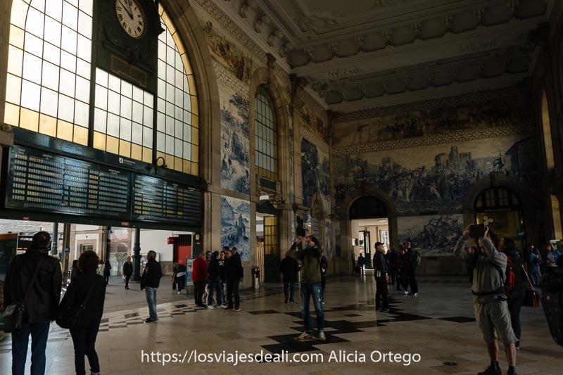 vestíbulo de la estación con dos chicos haciendo fotos a los azulejos y otros mirando los horarios de trenes