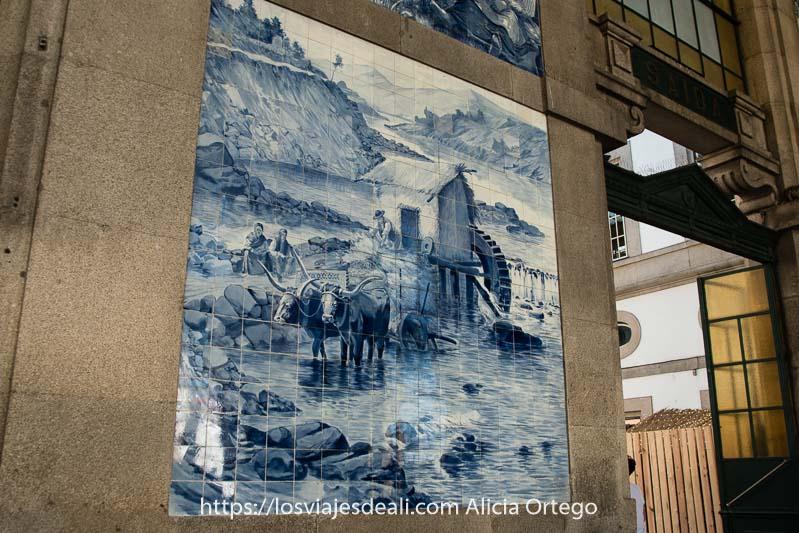 panel de azulejos en tonos azules con un molino en el río y un carro tirado por dos bueyes con enormes cuernos