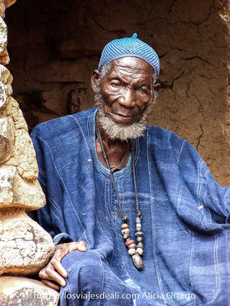 fotos de Mali: anciano Dogón con gorrito azul, chilaba de algodón azul y collar de bolas grandes de cerámica y barba blanca