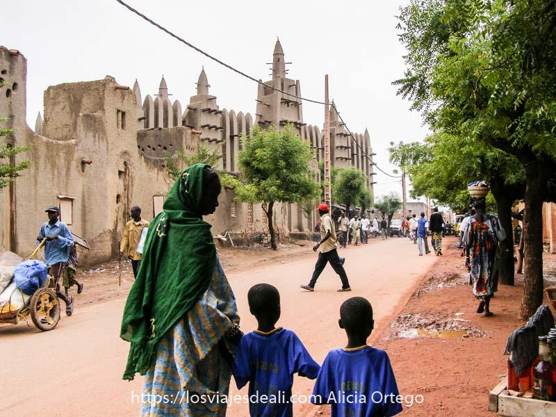 calle de Mopti con mezquita saheliana al fondo y en primer plano una mujer con chal verde lleva a dos niños con la misma camiseta de la mano