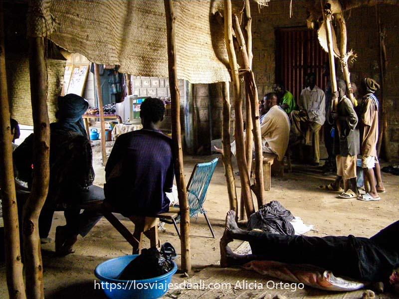 fotos de Mali: hombres y niños viendo la tele en un patio con techo de esterillas con la luz entrando por detrás