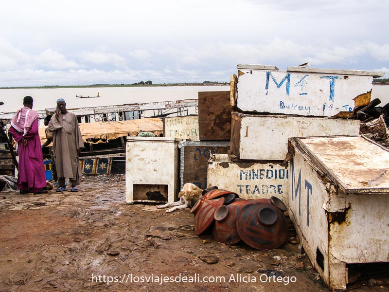 orilla del rio niger en Mopti con dos hombres con chilaba una marrón y otra rosa y un montón de cajones viejos al lado