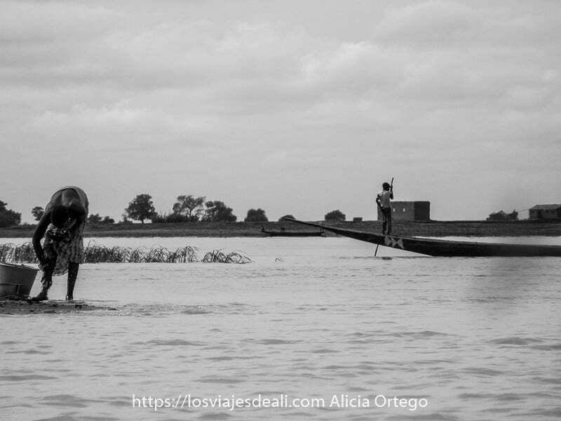 fotos de Mali escena del río níger con joven llevando barca con pértiga a la derecha y mujer lavándose las piernas a la izquierda