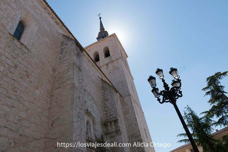 torre de la iglesia de colmenar de oreja con el sol detrás y una farola con 5 brazos