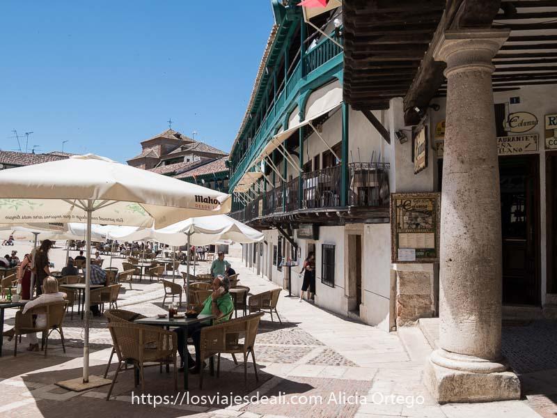 rincón de la plaza mayor con columna de granito grande y terraza con gente tomando algo