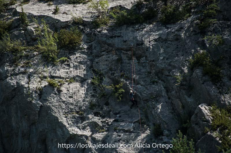 chica escalando una pared de roca con cuerdas y casco