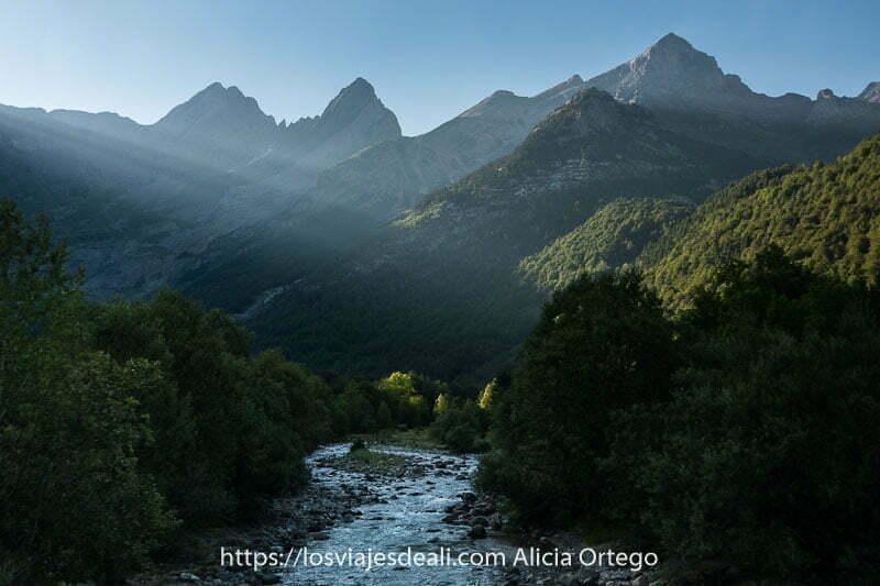 Valle de Pineta con río cinca y rayos de sol entrando por la derecha y al fondo varios picos