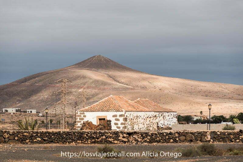 paisaje de Fuerteventura con casas blancas y volcán detrás en tonos beige