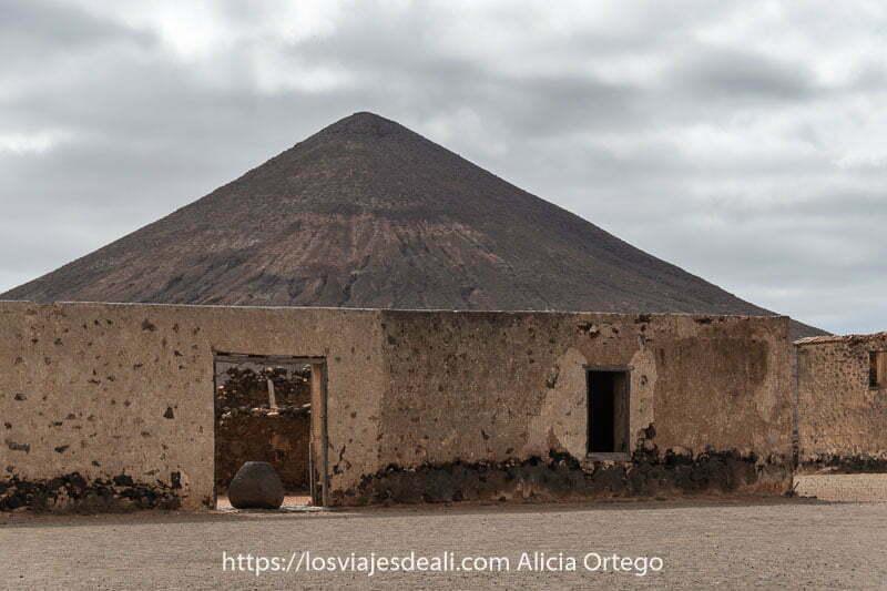 montaña del frontón de forma cónica perfecta y un edificio en ruinas en la oliva