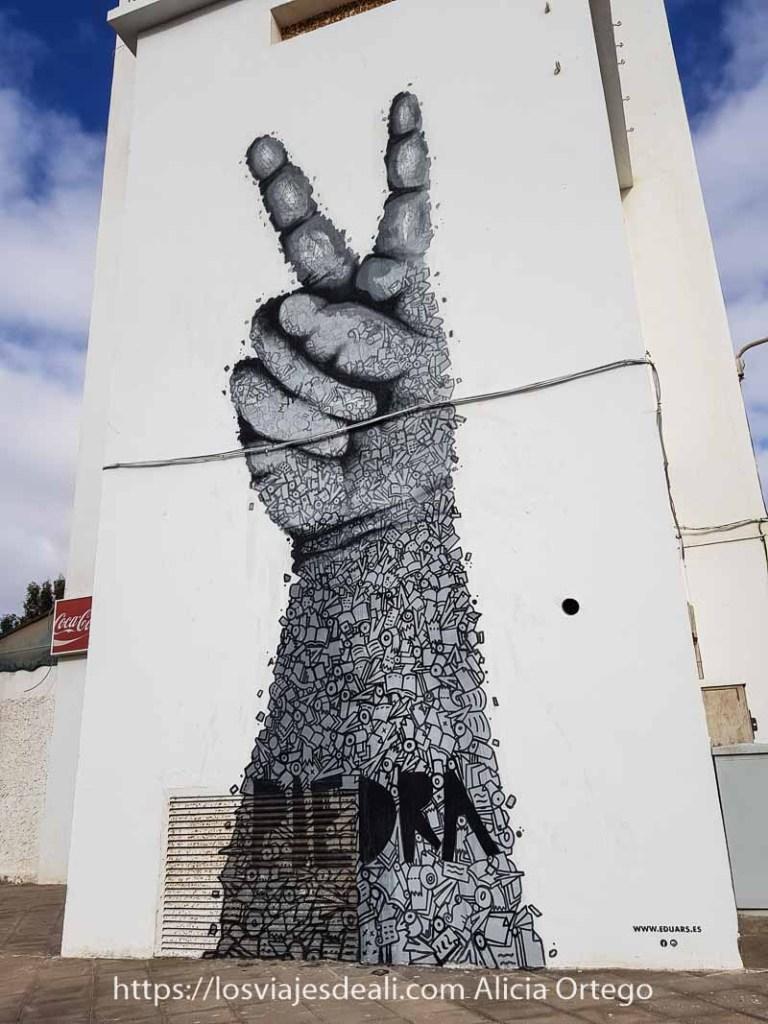 mural de puerto del rosario con un brazo y una mano con signo de V