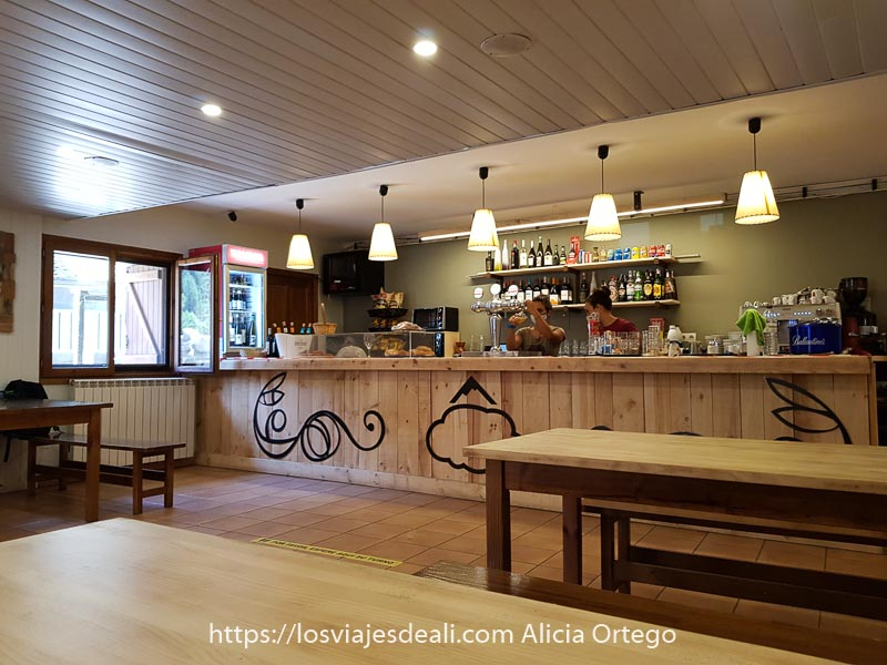 interior del refugio de Bujaruelo con mobiliario y barra de bar de madera de pino