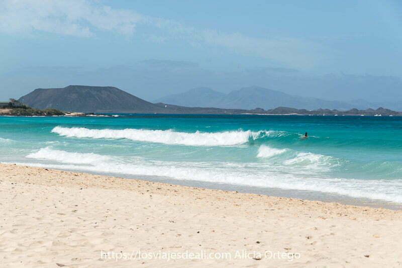 playa con mar de colores verdes y azules y la isla de lobos al fondo