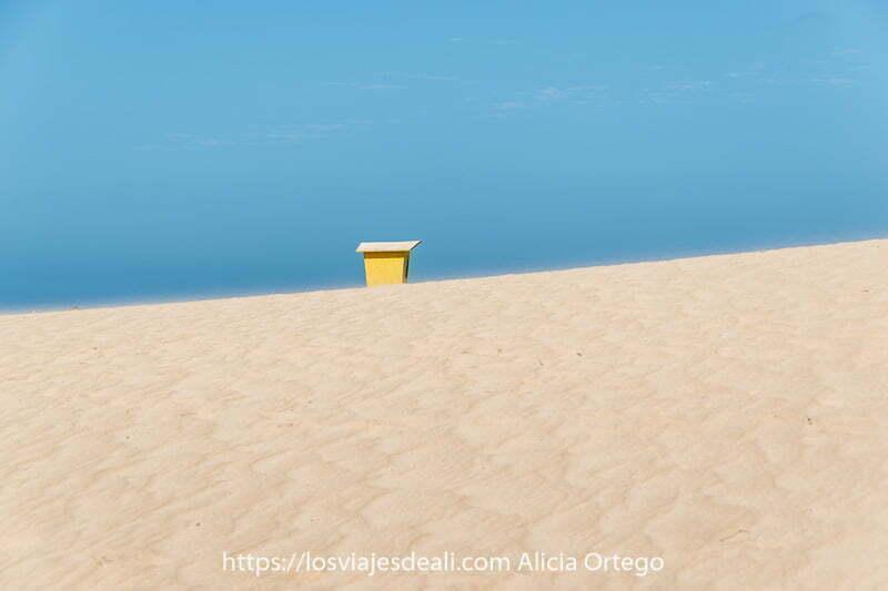caseta de socorrita asomando tras una duna de arena levantada por el viento y cielo muy azul