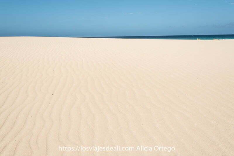 gran extensión de arena casi blanca con líneas dibujadas por el viento y un poco de mar de color turquesa al fondo
