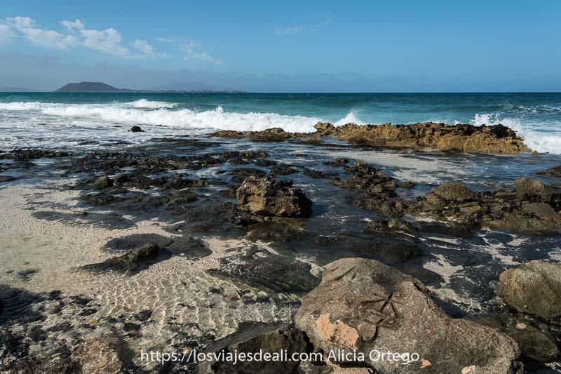 orilla del mar con rocas volcánicas y olas rompiendo en ellas y al fondo la isla de lobos