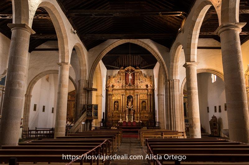 interior de la iglesia de betancuria con altar barroco dorado y columnas de piedra que soportan arcos