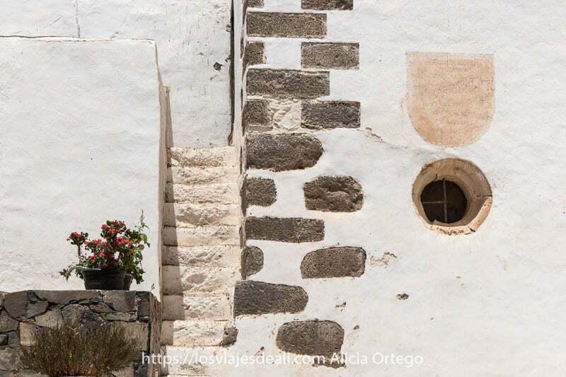 esquina de la torre de la iglesia con sillares de roca gris volcánica y unas escaleras estrechas entre muros encalados