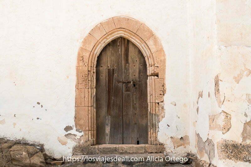 puerta de la ermita con arco apuntado en piedra beige y cerrojo de hierro en betancuria