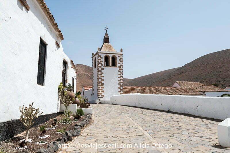 calle de betancuria empedrada con casas de un piso blancas y al fondo la torre de la iglesia