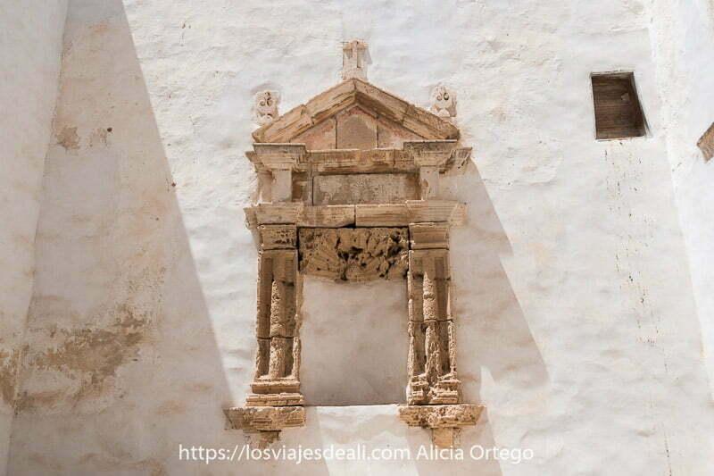 altar de piedra con forma de templo griego empotrado en pared blanca en las ruinas del convento