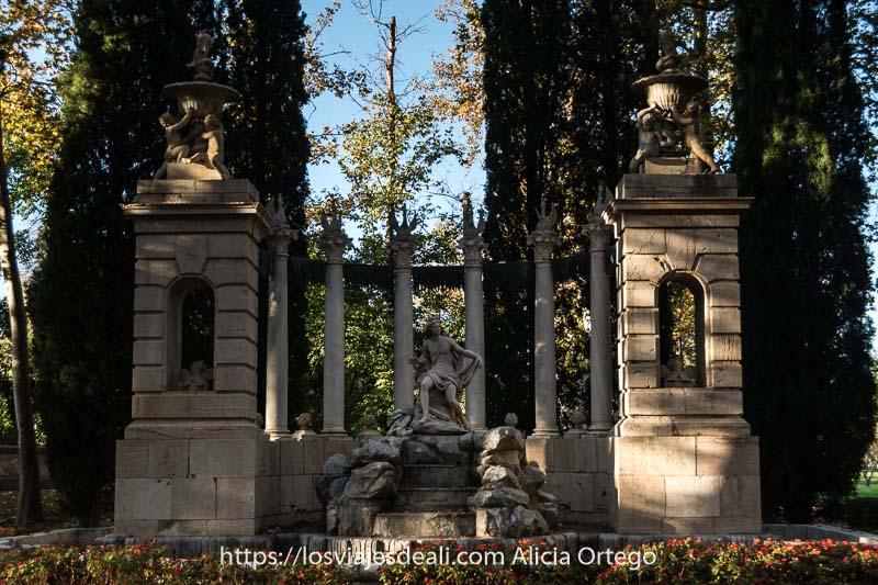 fuente de Neptuno neoclásica con varios cipreses detrás en el jardín del príncipe de Aranjuez