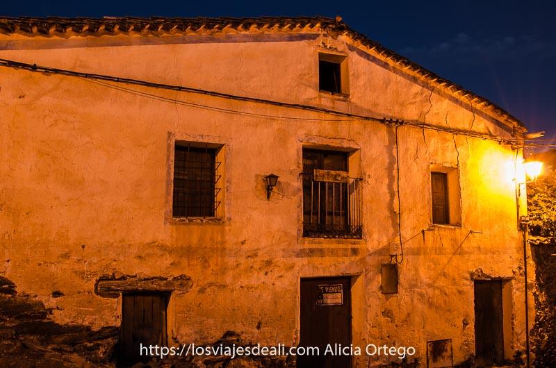 casa de patones con fachada blanca iluminada por farola al anochecer y cartel de se vende