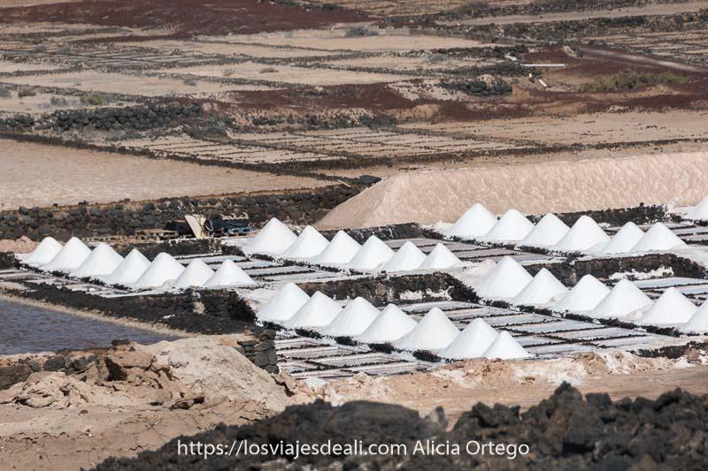 lugares que ver en Lanzarote las salinas de janubio con montones de sal en forma de pequeñas pirámides