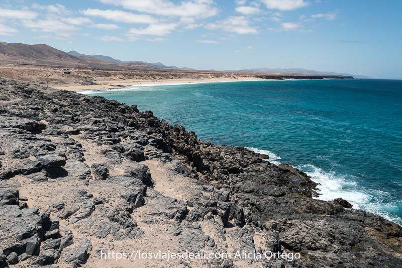 paisaje de acantilados volcánicos y playas de arena blanca con mar de color turquesa en El Cotillo