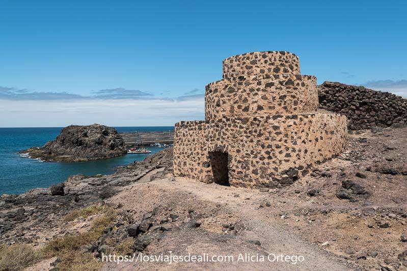 horno de cal con forma de pequeña pirámide escalonada junto a acantilados y puerto detrás