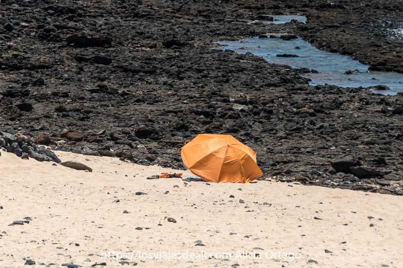 sombrilla de color naranja sobre arena blanca y delante rocas negras volcánicas