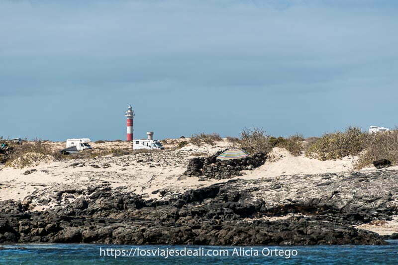 costa rocosa con arena blanca y faro pintado a líneas blancas y rojas en el horizonte en El Cotillo