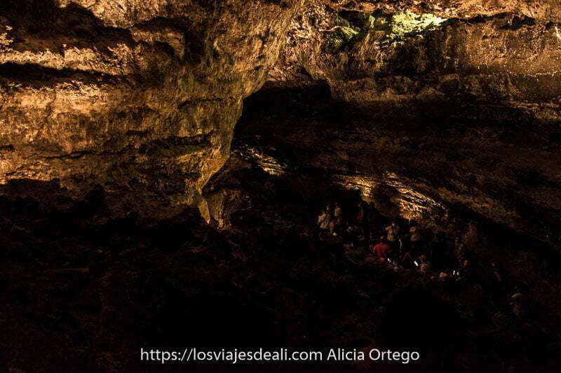 visitantes de la cueva de los verdes en una gran galería de roca volcánica