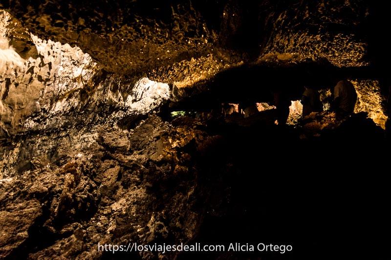 visitantes andando entre los techos bajos de la cueva de los verdes