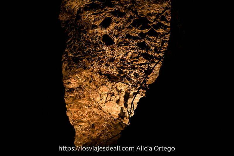 pared de la cueva de los verdes llena de oquedades y barandilla de escalera que sube en curva