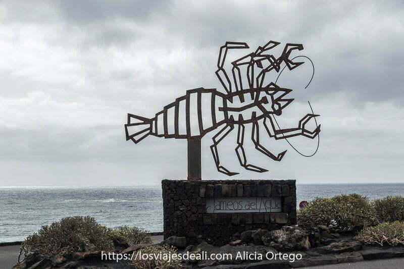 cartel de los jameos del agua con el mar detrás y un gran escorpión de hierro que es su símbolo