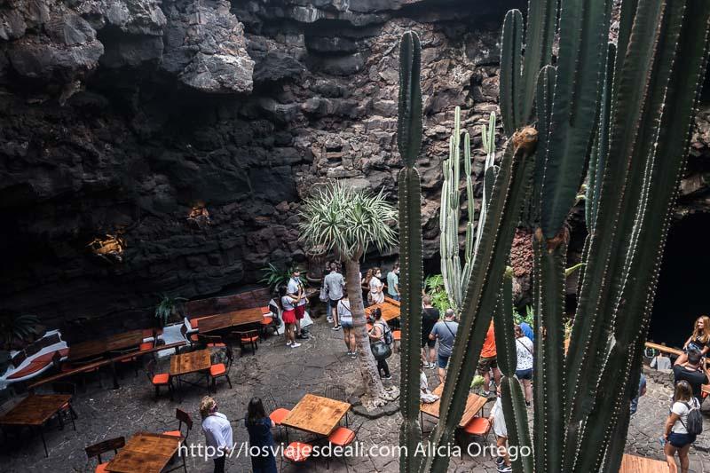 gente visitando los jameos del agua con grandes cactus alrededor y mesas y sillas de cafetería