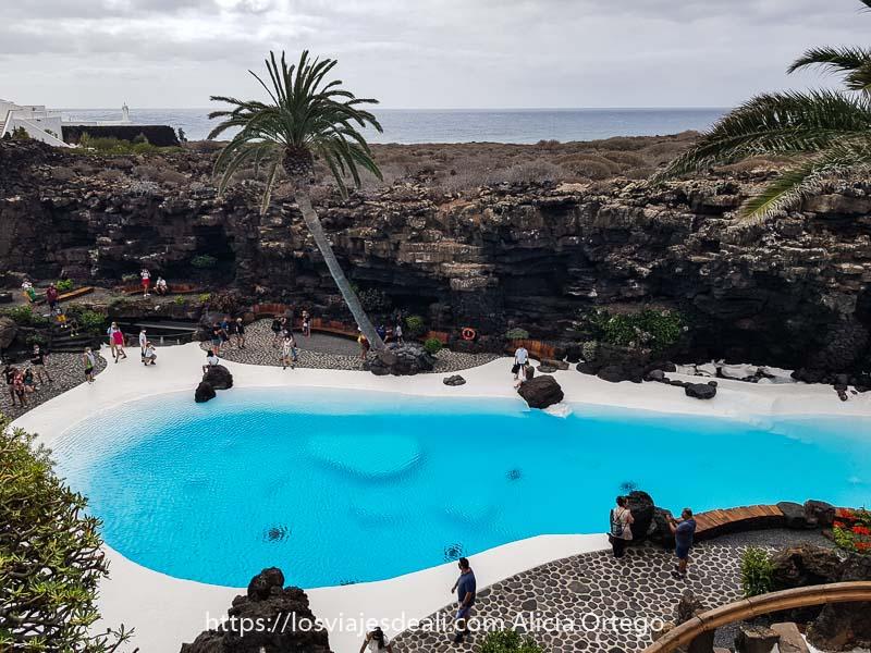 piscina de los jameos del agua pintada de blanco con agua muy azul y con palmera inclinada