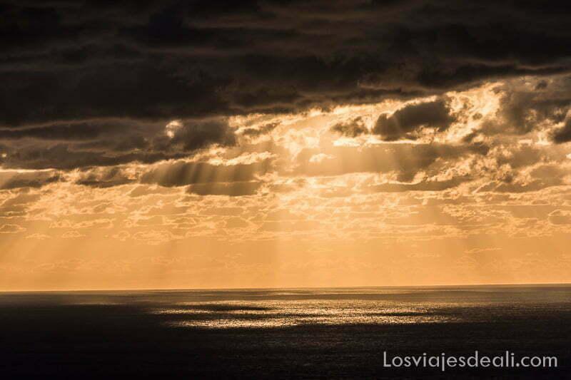 horizonte de mar al atardecer con rayos del sol traspasando las nubes en abanico hacia abajo