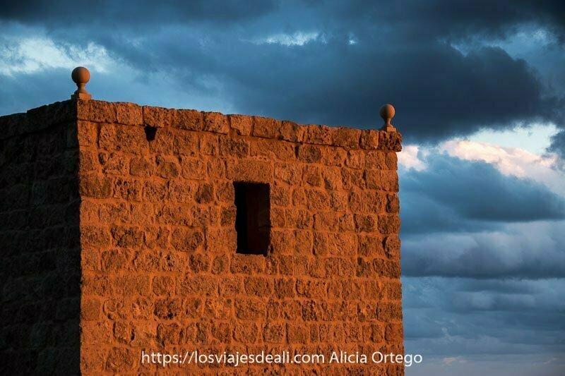 torre de piedra con bolas en las esquinas superiores y una ventana oscura iluminada por sol poniente