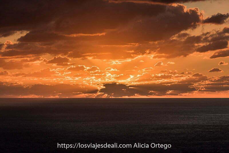 nubes oscuras con luz del sol delineando sus contornos en tonos naranjas