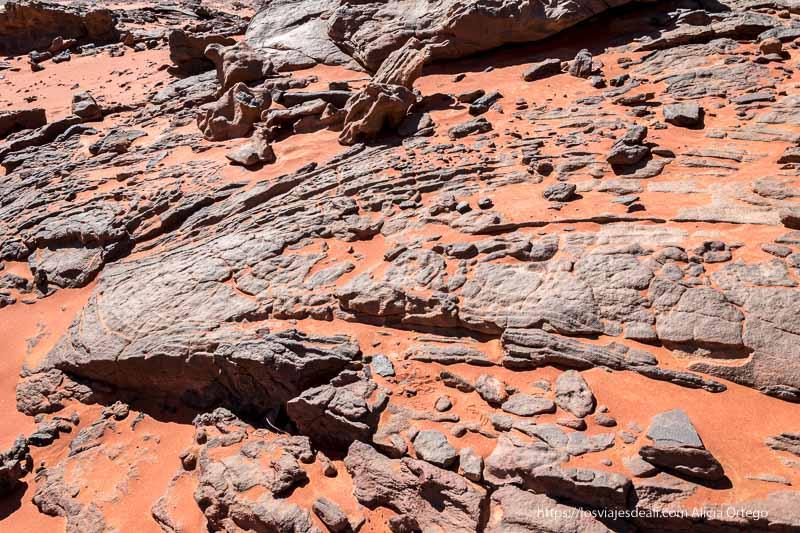 detalle del suelo con roca basáltica de color gris y arena roja