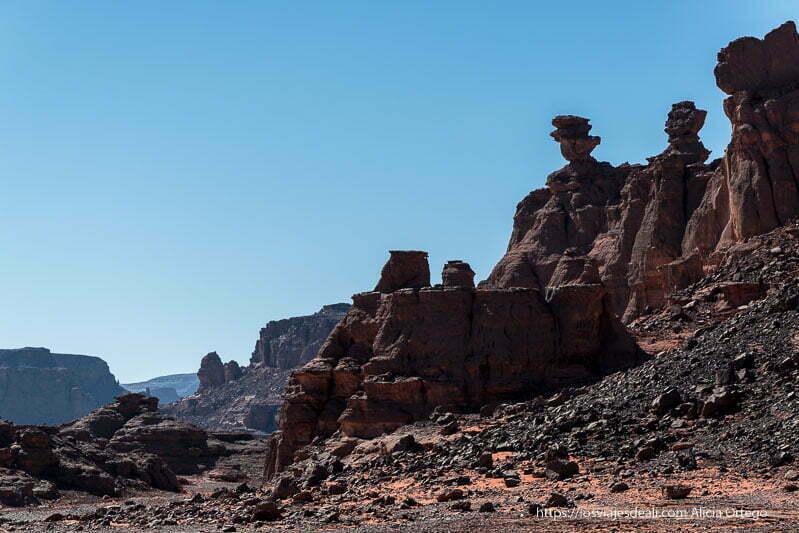 paisaje de rocas basálticas de color negro formando torres y mesetas que se pierden en el horizonte con cielo muy azul