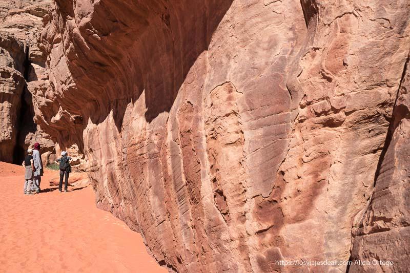 pared de roca arenisca con signos de humedad y suelo de arena y al fondo un tuareg y dos viajeros mirando la pared