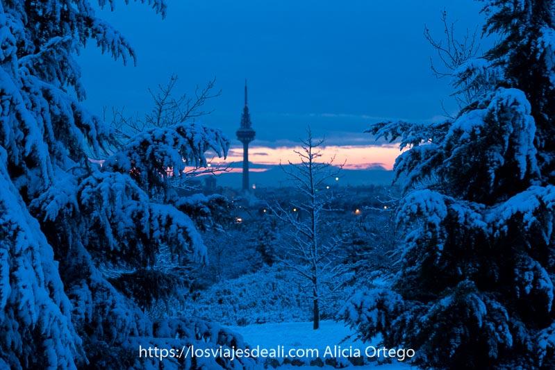 pirulí destacando en el horizonte con franja rojiza y resto muy azul lleno de nieve en madrid