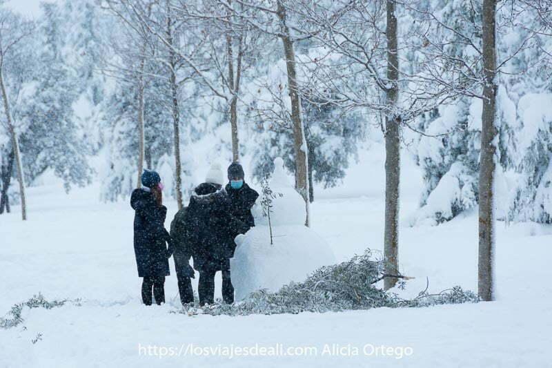 un grupo de chicos haciendo un gran muñeco de nieve en el parque